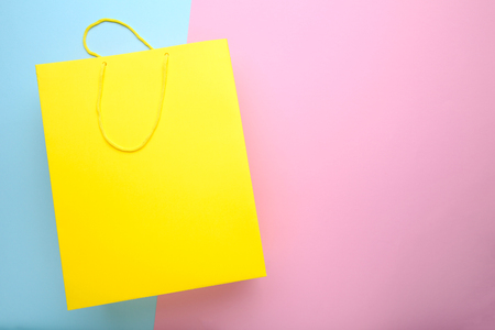 Paper shopping bag on colorful background