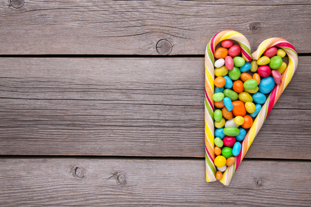 Colorful lollipops and different colored round candy on grey