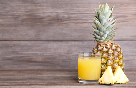 Fresh pineapple juice in the glass on grey wooden background Imagens