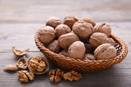 Walnuts kernels in basket on grey wooden background. Walnuts kernels on grey wooden table Imagens