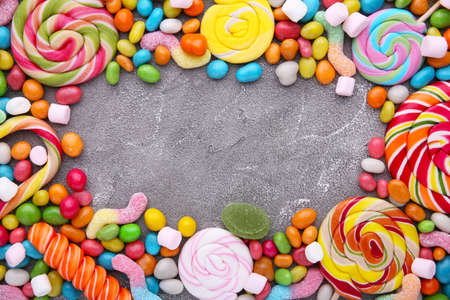 Colorful lollipops and different colored round candy on concrete