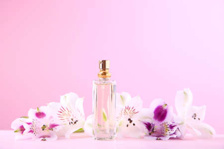 Bottle of perfume with flowers on pink background with copy space