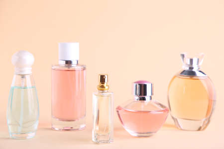 Many perfume bottles on a beige background, top view Stock Photo