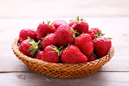 Ripe strawberries in the basket on gray wooden background, macro