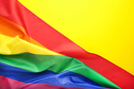 Rainbow LGBT flag on yellow background, top view Archivio Fotografico