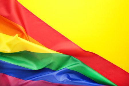 Rainbow LGBT flag on yellow background, top view Stockfoto