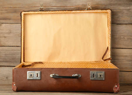 Open old shabby leather portable suitcase for travel trip on gray wooden background. Top view