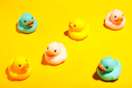 Collection of colorful rubber ducks on a yellow background. Top view Reklamní fotografie
