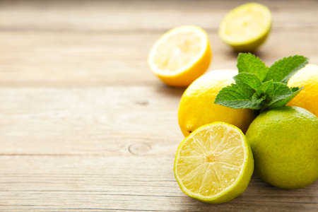 Fresh ripe citruses with mint on garden wood table. Lemon and lime Stockfoto