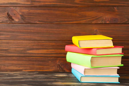 Multi colored school books on brown wooden background with copy space. Top view Imagens