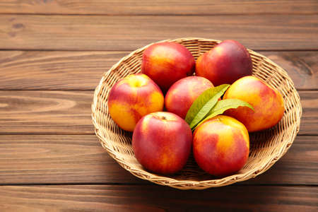 Nectarines in a basket on brown background with copy space. Top view
