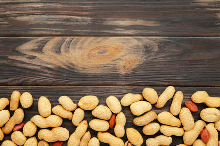 Peanuts in shells on brown wooden background. Top view