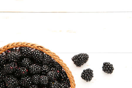 Blackberry in a wicker basket on a white wooden background. Top view Stock Photo