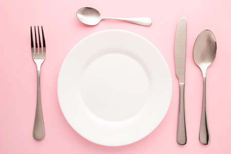 Table setting with white plates, and cutlery - fork, spoon and knife. Shot from above. Copy space on empty plate. Stockfoto