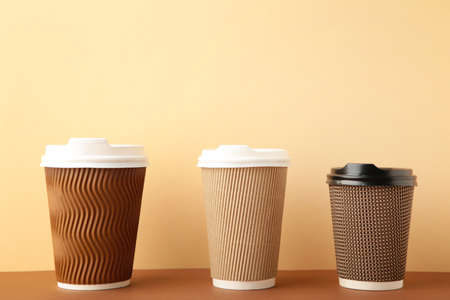 Three brown cups of coffee on beige background. Top view