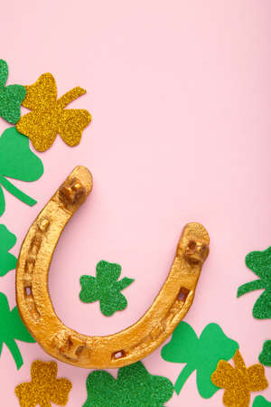 Green clovers and gold horseshoe on pink background for St. Patrick's Day Holiday. Top view.