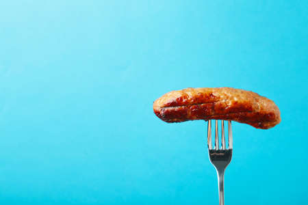 Grilled sausage on a fork on blue background with copy space. Top view. Vertical foto