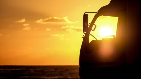 He stopped the car in the evening on the seashore. A truck is parked on the beach. The sun shines in the cockpit.