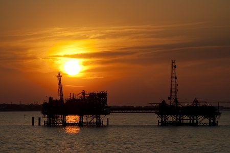 Oilrig in the sunset Фото со стока
