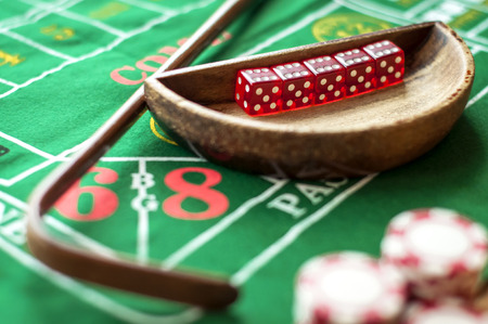 5 Dice in a bowl and a stick on a craps table