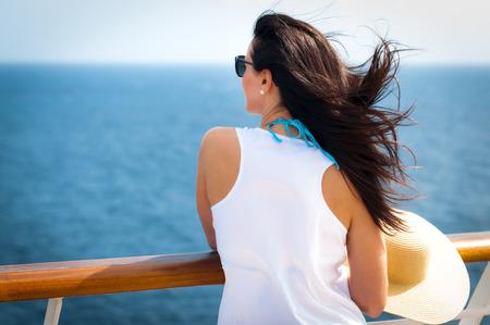 cielo y mar: La mujer llevaba un sombrero de paja de disquete y un vestido blanco de pie junto a la barandilla en un crucero Foto de archivo