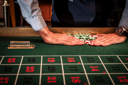 bets: Casino dealer clearing the losing bets