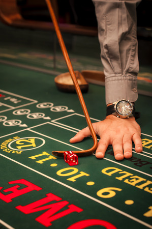 craps: Casino dealer pushing a pair of dice on a craps table Stock Photo