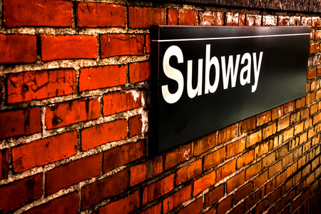 Subway sign on  red brick wall at night in Manhattan, New York