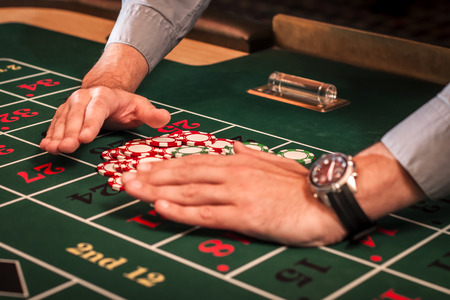 bets: Casino dealer is clearing the table of the losing bets Stock Photo