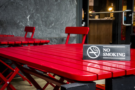 No smoking sign on a red table in a outdoor restaurant