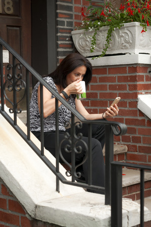 stoop: Woman having a coffee in front of her house on the stairs Stock Photo