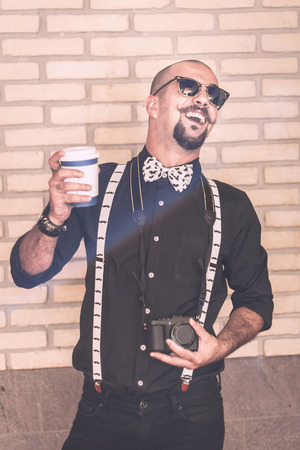 cocky: Pretentious hipster having an annoying laughter wile holding his coffee and his camera