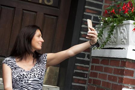 stoop: Woman taking a selfie in front of her door on the front stoop