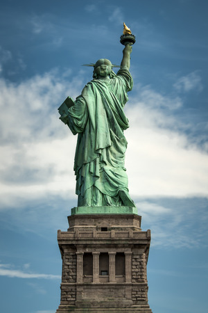 newyork: Statue of liberty seen from the back with a cloudy sky as background