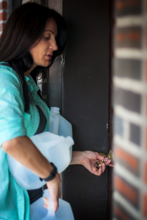 front stoop: woman struggling to open the door to her home because of the heavy bottled water she is holding Stock Photo