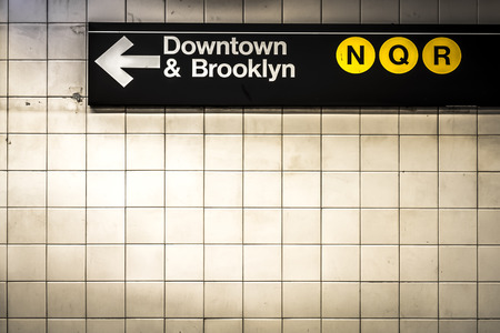 Subway sign in Manhattan directing passengers  and travelers to the downtown and Brooklyn trains Фото со стока