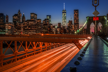Brooklyn bridge at night with light trails formed by the moving cars