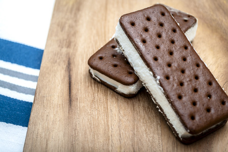 ice cream chocolate: Image with a rustic feeling of two Ice Cream sandwiches on a wooden table Stock Photo