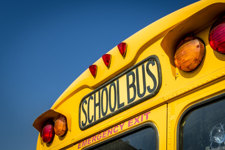 Closeup of a school bus from the back with the stop lights and the emergency exit visible Stock Photo