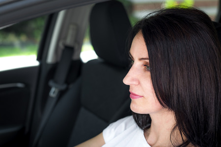 Woman in her late 30s to early 40s in a car happy to have passed the driver's license test