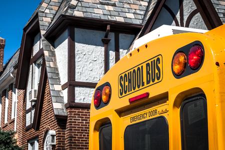 salida de emergencia: Primer plano de un autob�s de la escuela de la parte posterior con los sem�foros y la salida de emergencia visible en una zona residencial con una casa en el fondo