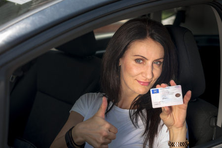 late 30s: Woman in her late 30s to early 40s in a car happy to have passed the driver's license test
