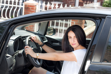 early 30s: Woman in her late 30s to early 40s in a car happy to have passed the driver's license test
