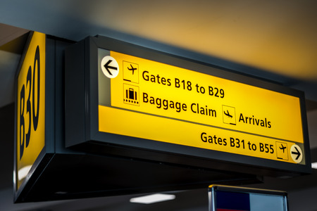 Yellow airport signage suspended by the ceiling in a terminal, telling passengers important information about their gates, where baggage claim, departures and arrivals are, etc Фото со стока