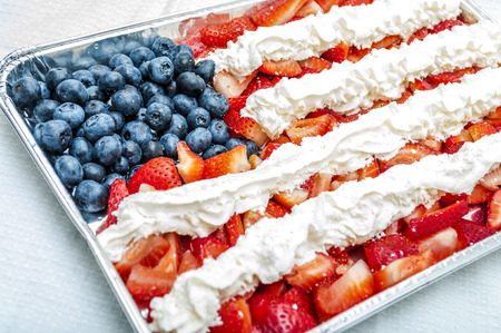 Whip Cream, strawberries and blueberries combined to look like the american flag and placed in a aluminium tray  for a 4th of july themed party
