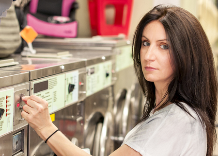 lass: Caucasian woman in her 30s is paying with coins for a load of laundry in a american laundromat