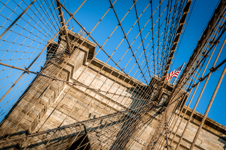 sates: Closeup of the Brooklyn Bridge in New York City, USA. The American flag is flying over the cloudless blue sky