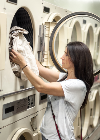lass: Caucasian woman in her 30s is checking her laundry in the dryer in a american laundromat Stock Photo