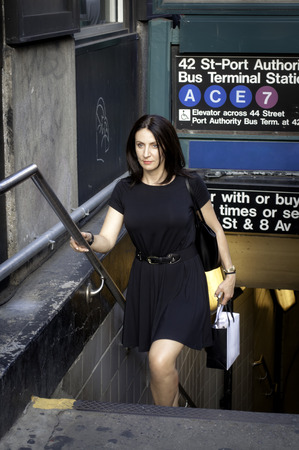 Corporate businees woman type coming out of the subway by climbing the stairs in Manhattan, NYC, holding a phone and a shopping bag