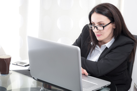 mature brunette: Mature brunette businesswoman is looking at the computer screen doing her paperwork, she is wearing a suit and glasses Stock Photo